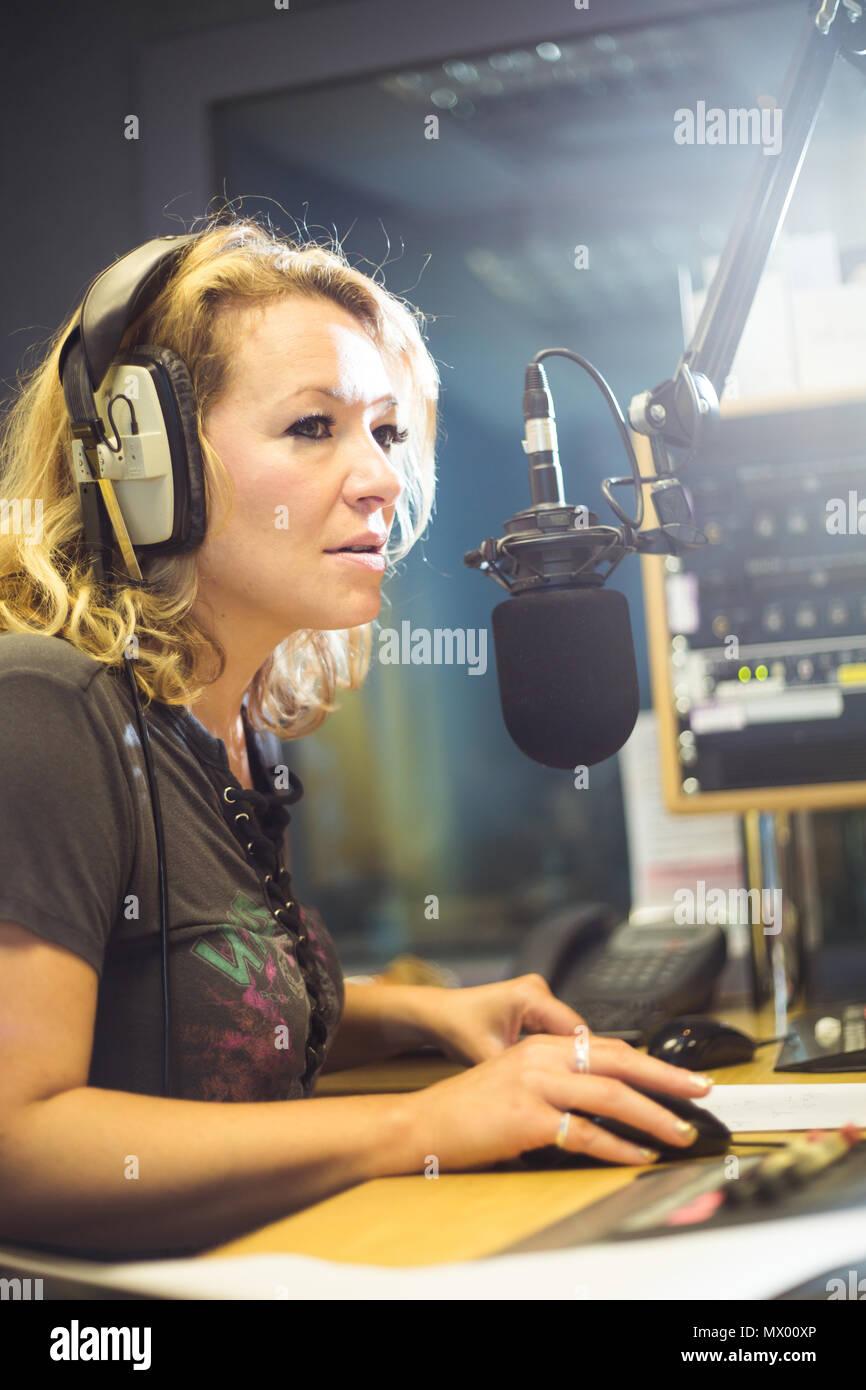 White British female DJ working inside recording studio with headphones Stock Photo