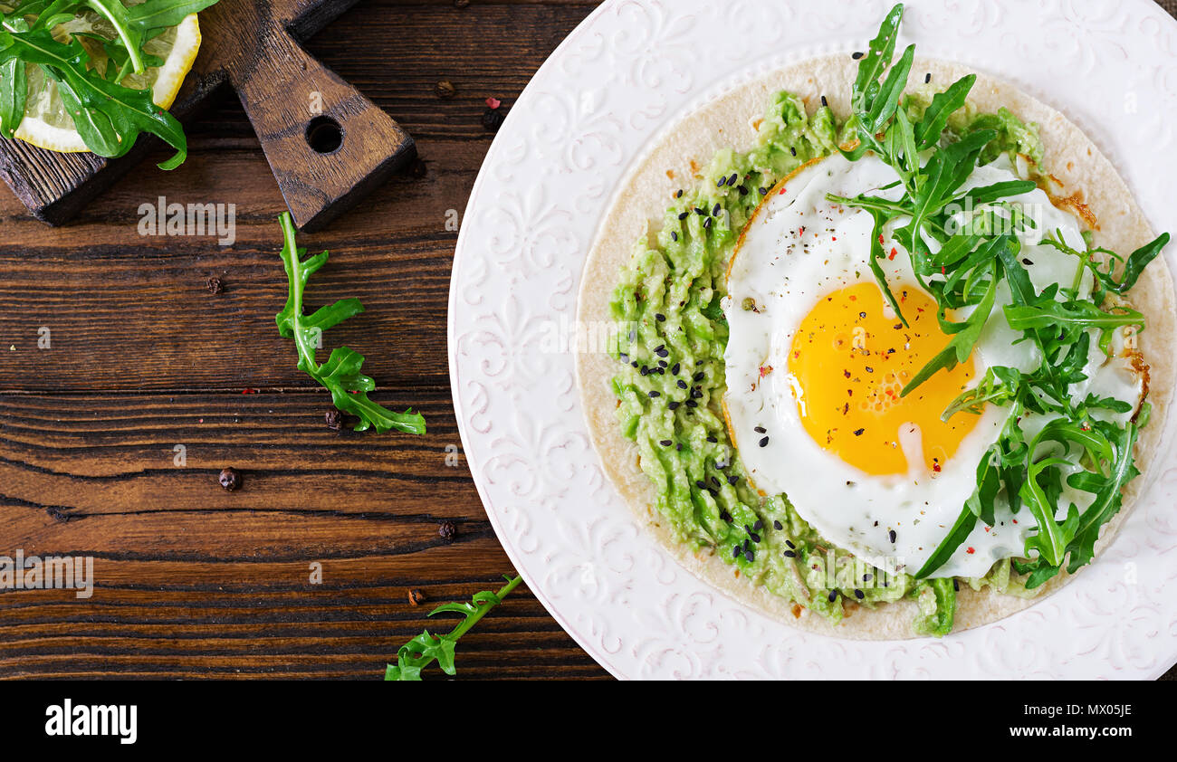 Tacos with guacamole, fried egg and arugula. Healthy food. Useful breakfast. Flat lay. Top view - Stock Image