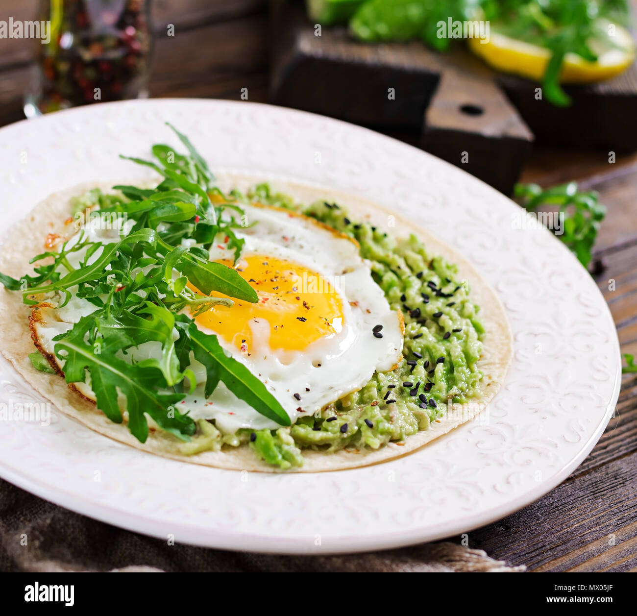 Tacos with guacamole, fried egg and arugula. Healthy food. Useful breakfast. - Stock Image