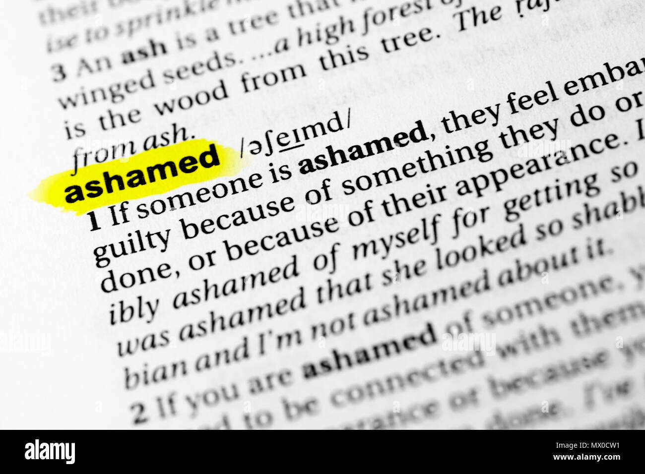 Highlighted English word 'ashamed' and its definition in the dictionary. - Stock Image