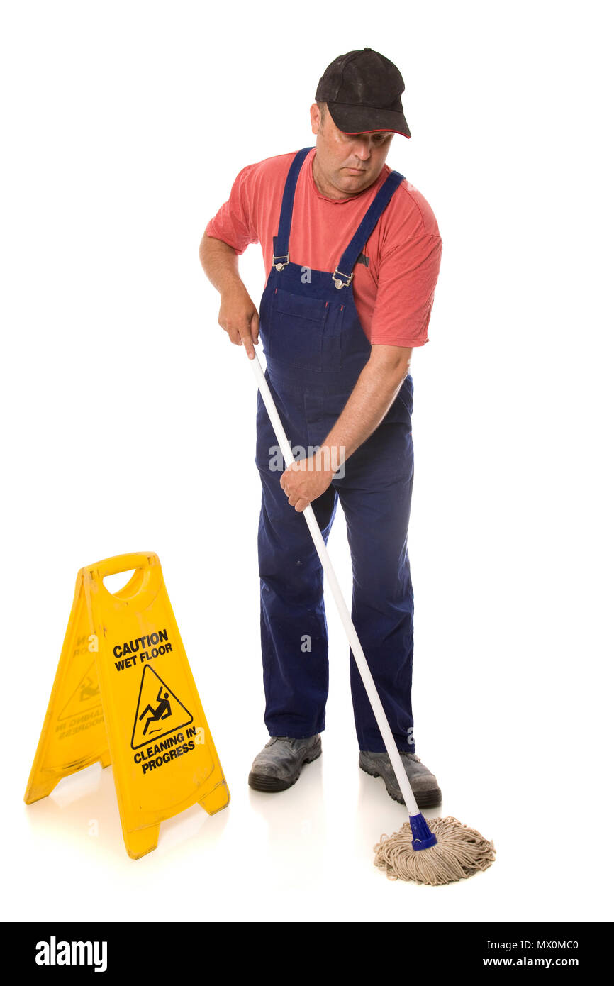 A person clearing up a slip hazard, using a warning sign for safety. - Stock Image