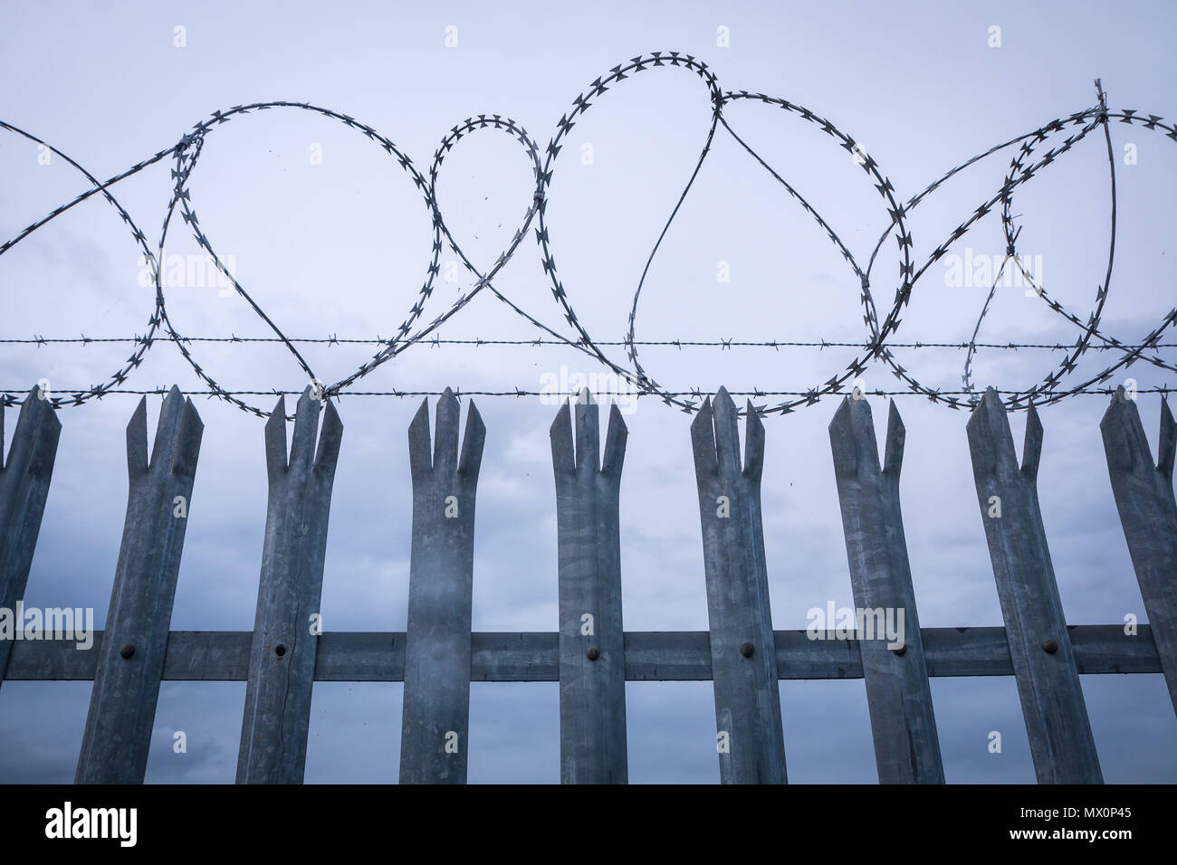 Barbwire on top of a fence - Stock Image