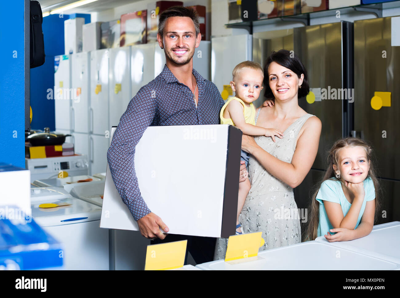 smiling american parents with two children shopping new electronics and holding box in shop of household appliances - Stock Image