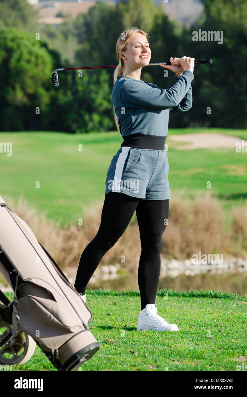 Female golf player is succeeded in ball hitting at golf course. - Stock Image