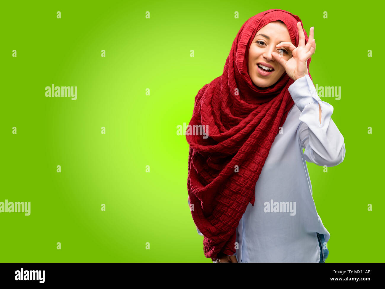 Young arab woman wearing hijab looking at camera through her fingers in ok gesture imitating