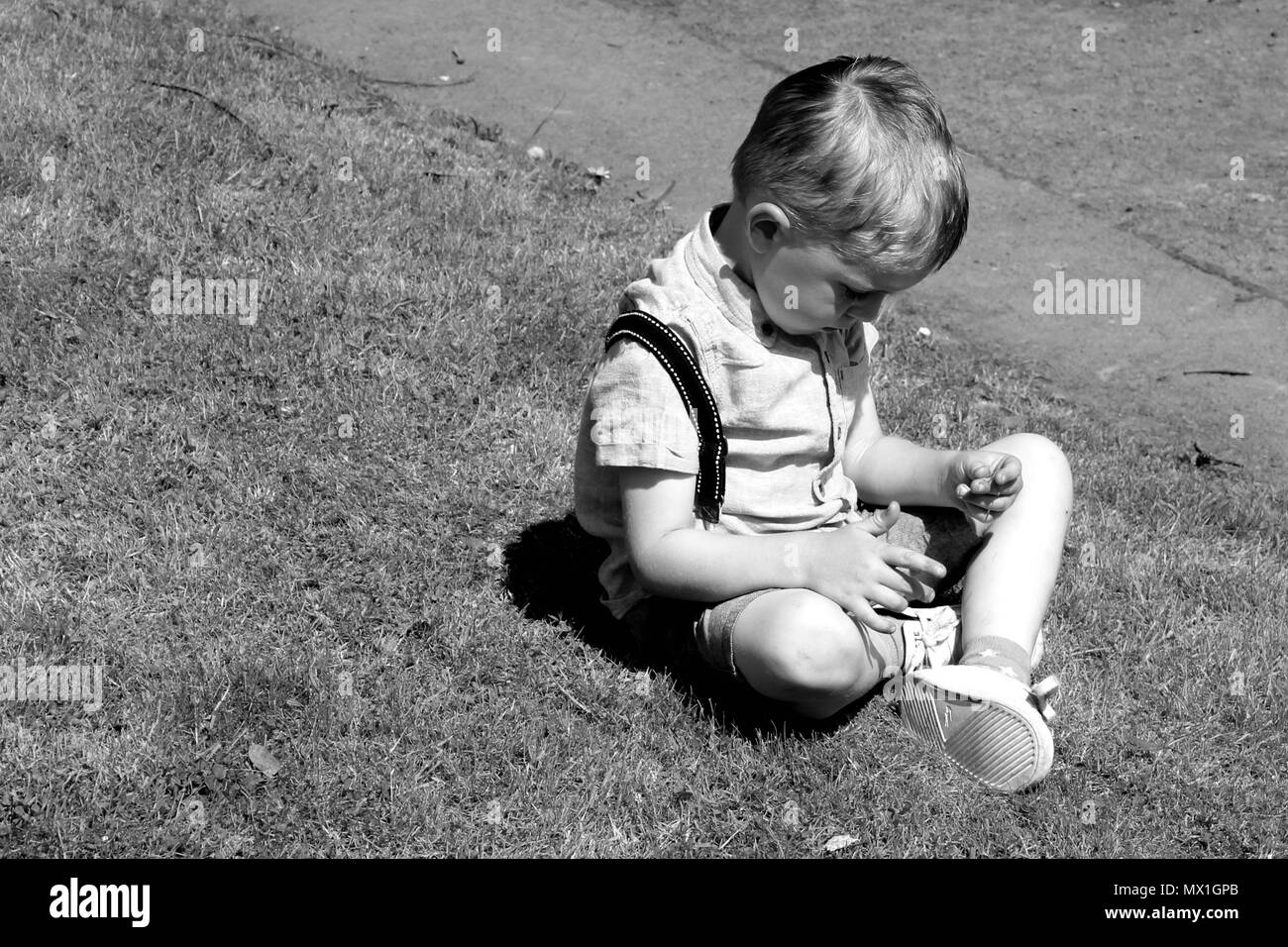 Young boy in deep thought sitting on grass black and white