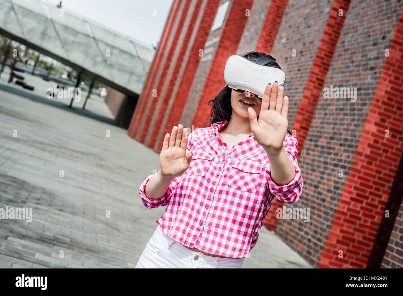 Virtual reality, fun in the park. A woman relaxes in the park using googles VR. The girl imagines that she is climbing the rope. Spending free time ou - Stock Image
