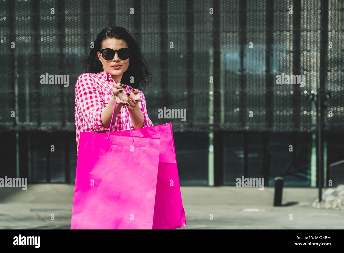 Happy and smiling girl enjoys shopping. Shopping concept. A young woman is satisfied with the things she bought. Female Walks or sit with Bags Full of - Stock Image