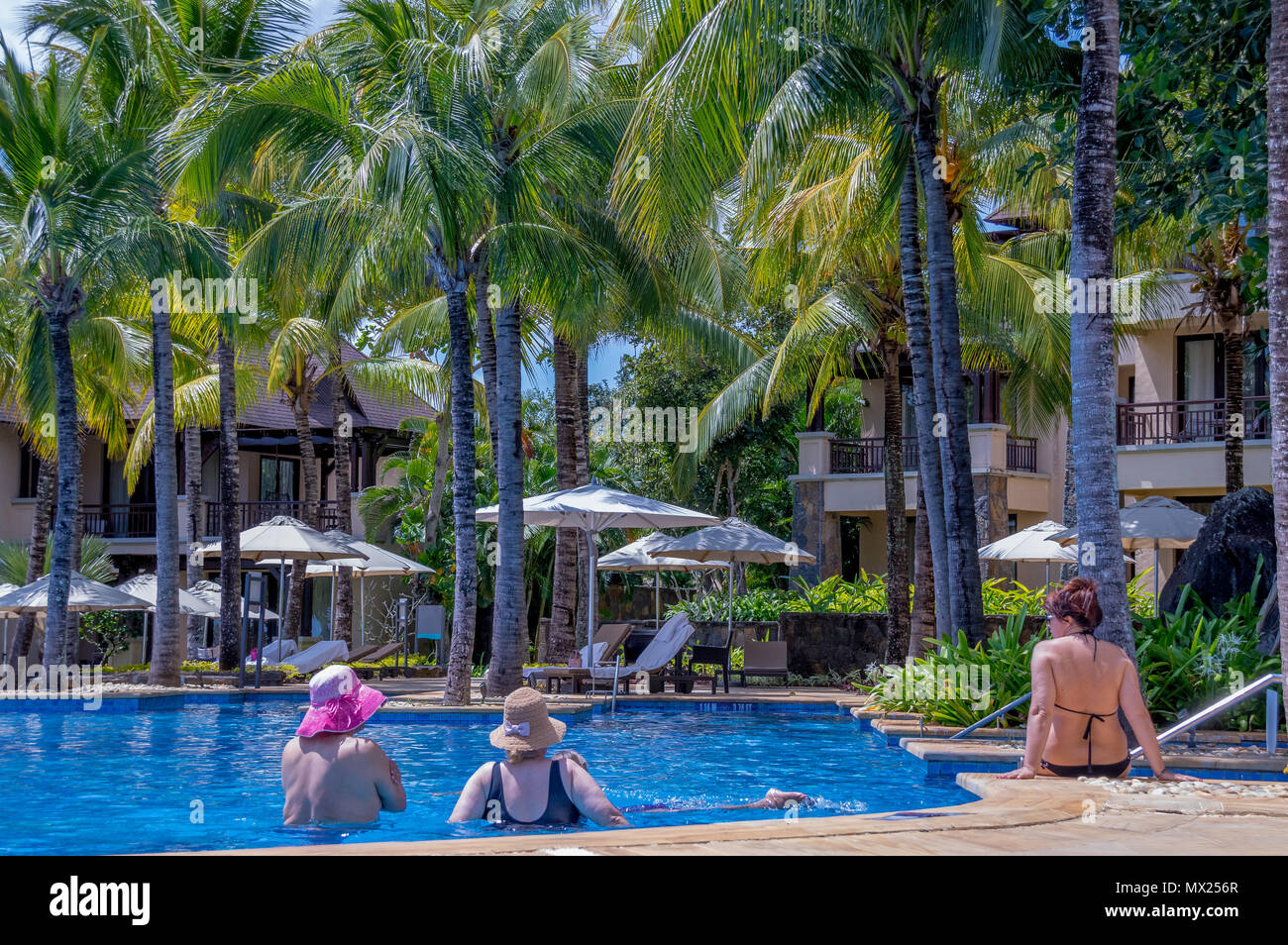 Balaclava, Mauritius - guests relaxing at the pool at the Westin Turtle Bay Resort and Spa image with copy space in landscape format - Stock Image