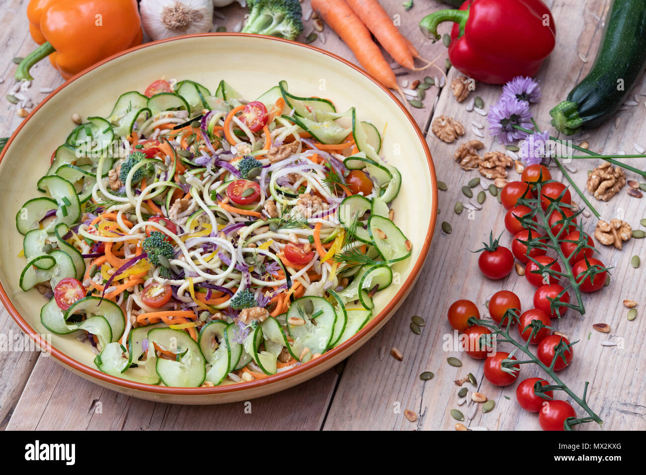 Spiralized Vegetable Salad in a bowl surrounded by vegetables on wood Stock Photo