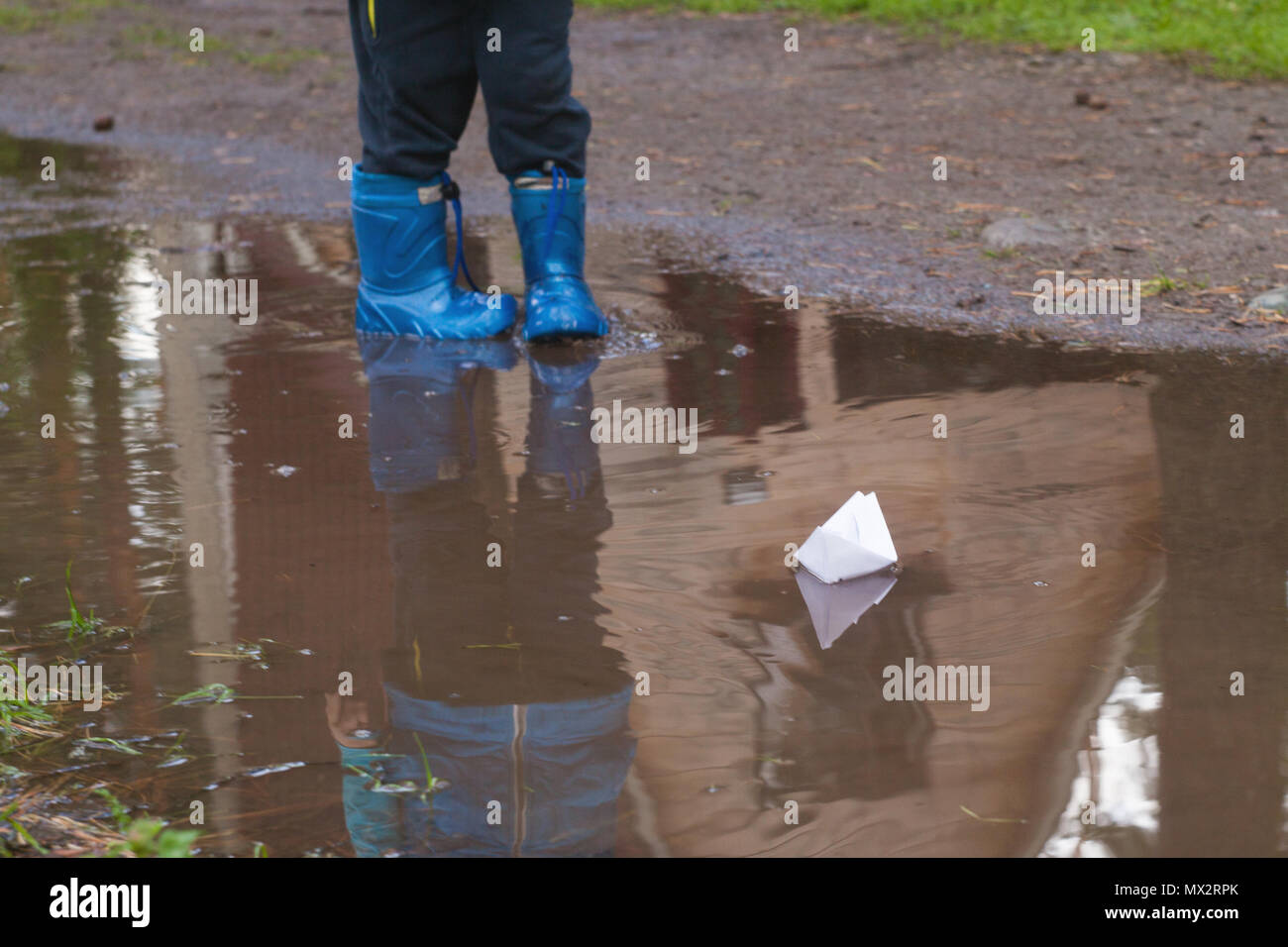 kid putting a paper boat into water - Stock Image