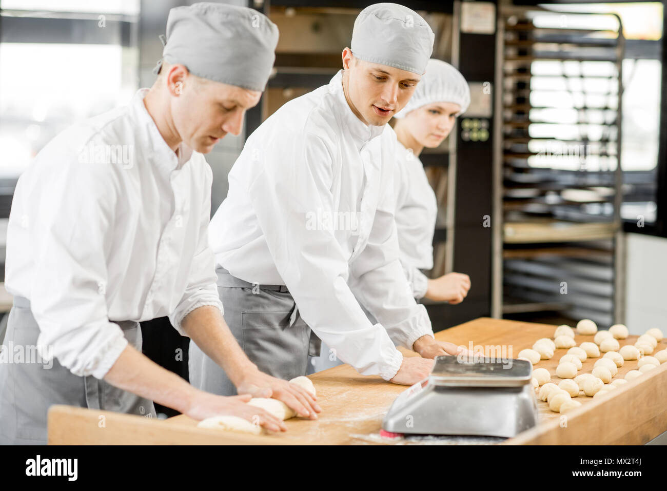 Bakers forming dough for baking at the manufacturing - Stock Image