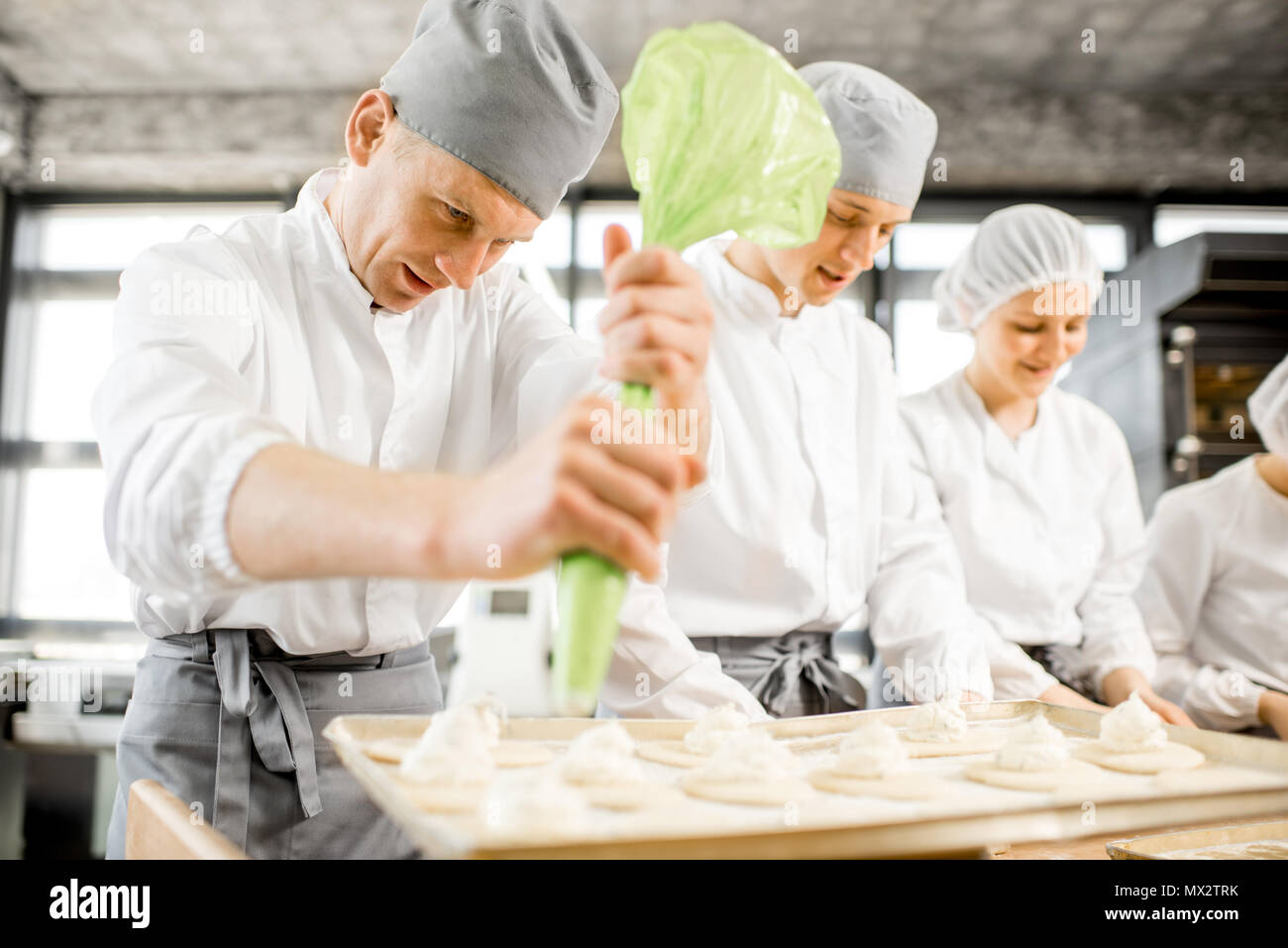 Bakers making buns at the manufacturing - Stock Image