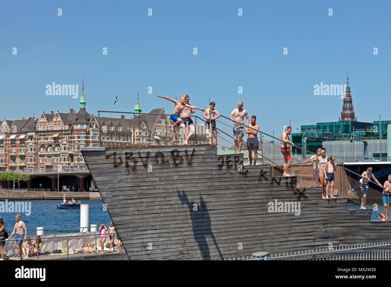 Boy jumping from the tower of Islands Brygge Harbour Bath in the beginning of the harbour bath season in Copenhagen, Denmark. Another warm summer day. Stock Photo