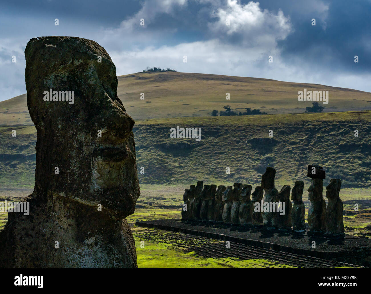 Tongariki Moai, largest reconstructed Ahu, Easter Island, Rapa Nui, Chile, with extinct volcano Poike in background - Stock Image