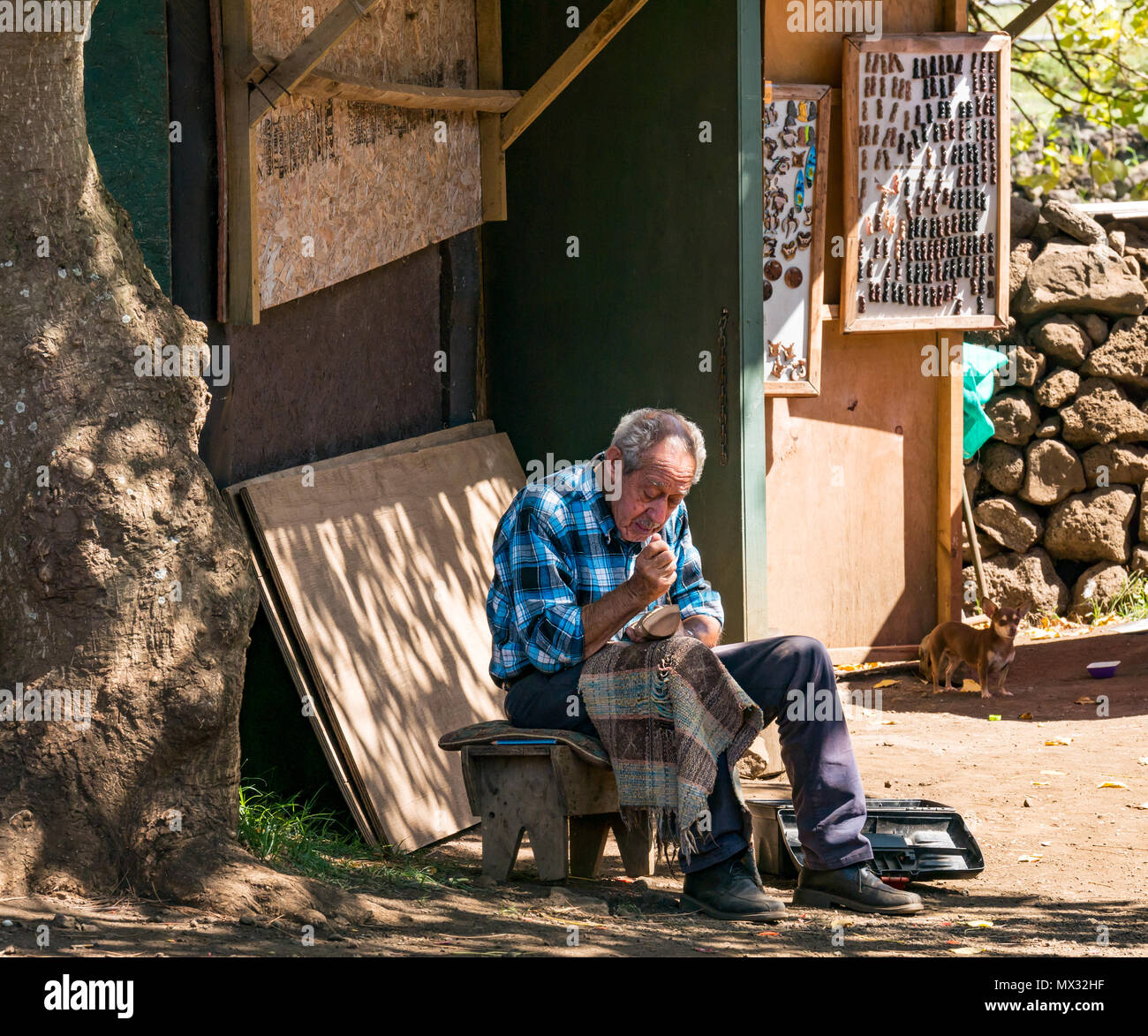 Old man hand sitting on stool in shade carving wooden Moai figure for sale to tourists, Rano Raraku quarry, Easter Island, Rapa Nui, Chile Stock Photo