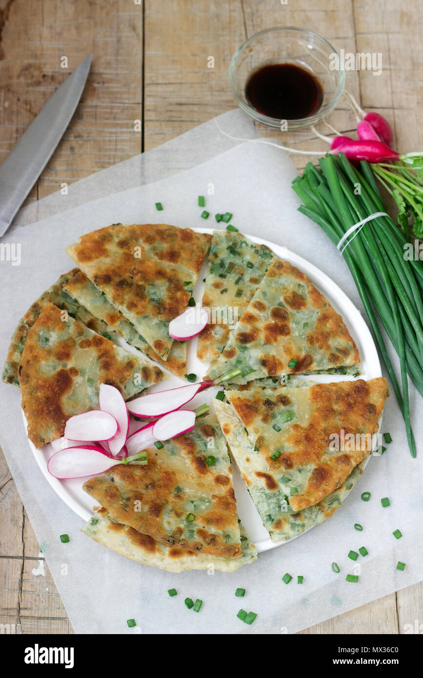 Homemade appetizing scallion pancakes with a bunch of green onions and radishes. Rustic style. Stock Photo
