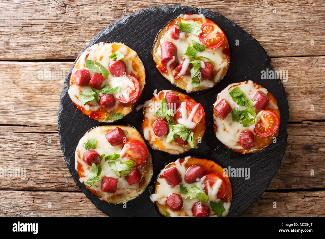 Pizza from baked eggplants with mozzarella, tomatoes, sausages and greens close-up on the table. Horizontal top view from above Stock Photo