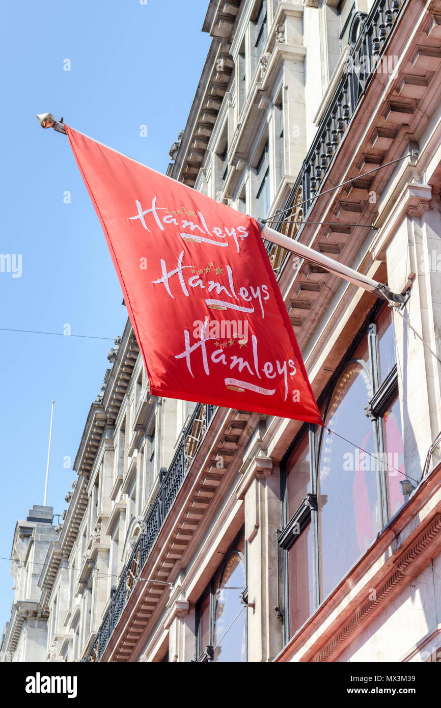 Red name flag flying outside Hamleys, the iconic popular toy shop in Regent Street, London W1 a major shopping street in the capital city, UK - Stock Image