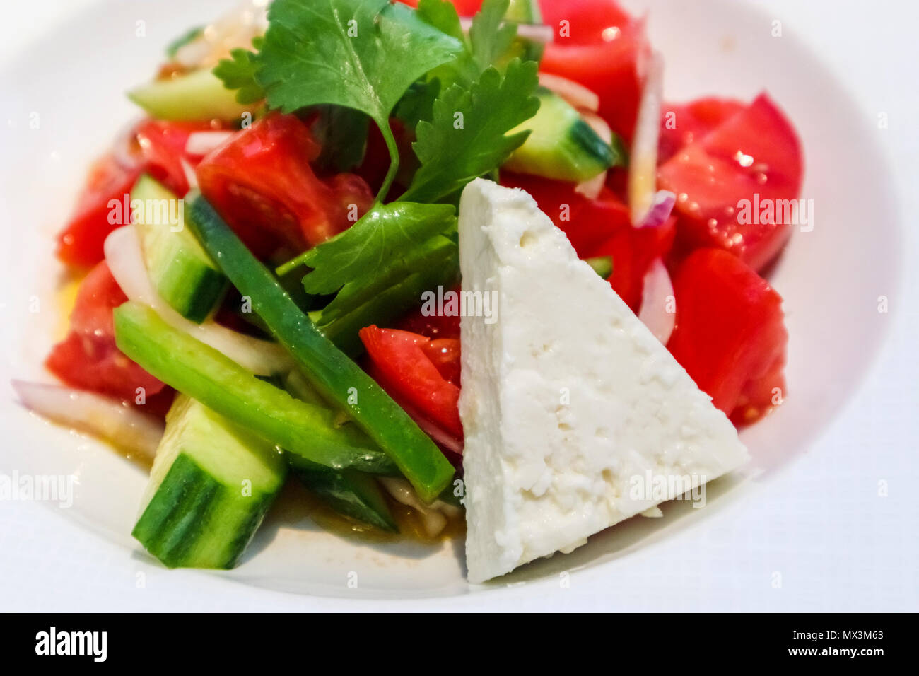 Fine dining hors d'oeuvres: Plate of healthy Greek salad as a first course, with feta cheese, chopped tomatoes, cucumber and a sprig of parsley - Stock Image