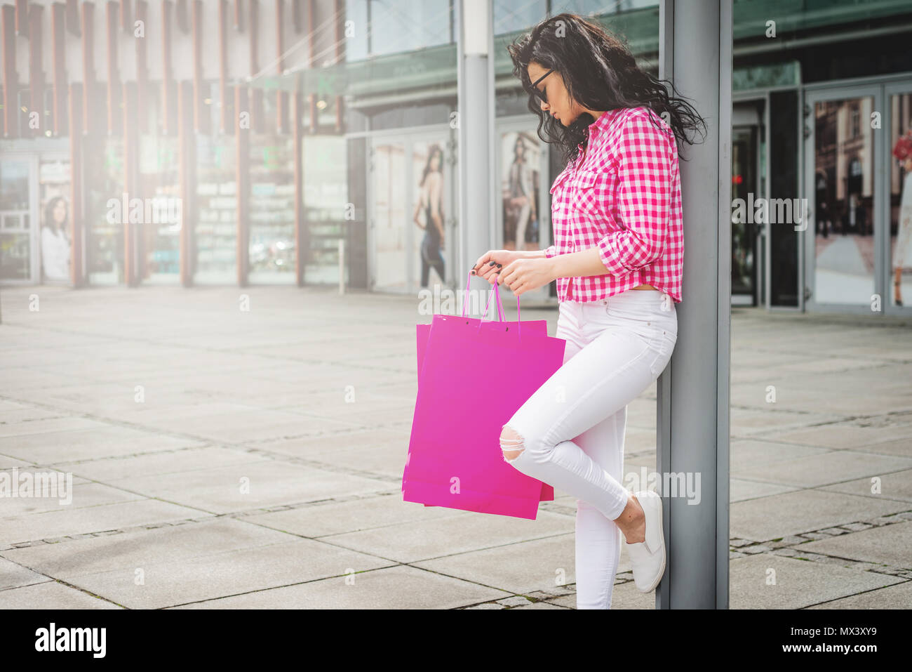 Happy and smiling girl enjoys shopping. Shopping concept. A young woman is satisfied with the things she bought. Female goes out with shopping bags fr - Stock Image