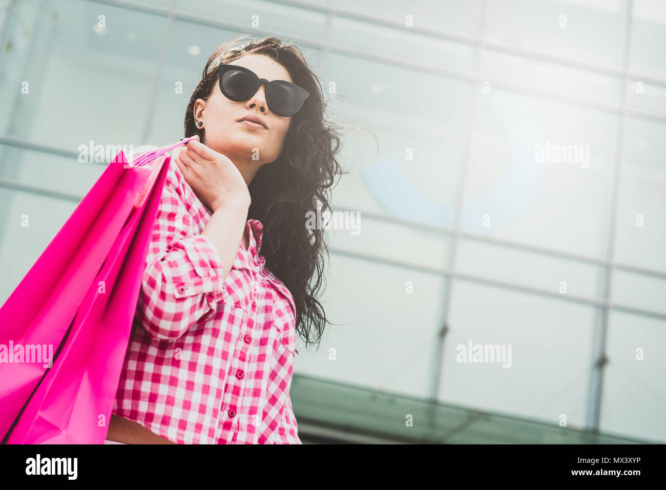 Happy and smiling girl enjoys shopping. Shopping concept. A young woman is satisfied with the things she bought. Female goes out with shopping bags. - Stock Image