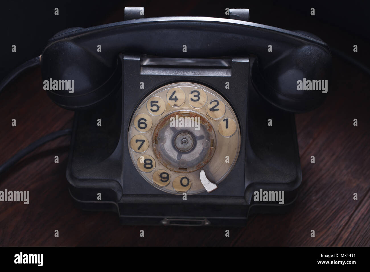 Old retro black phone on wooden board - Stock Image
