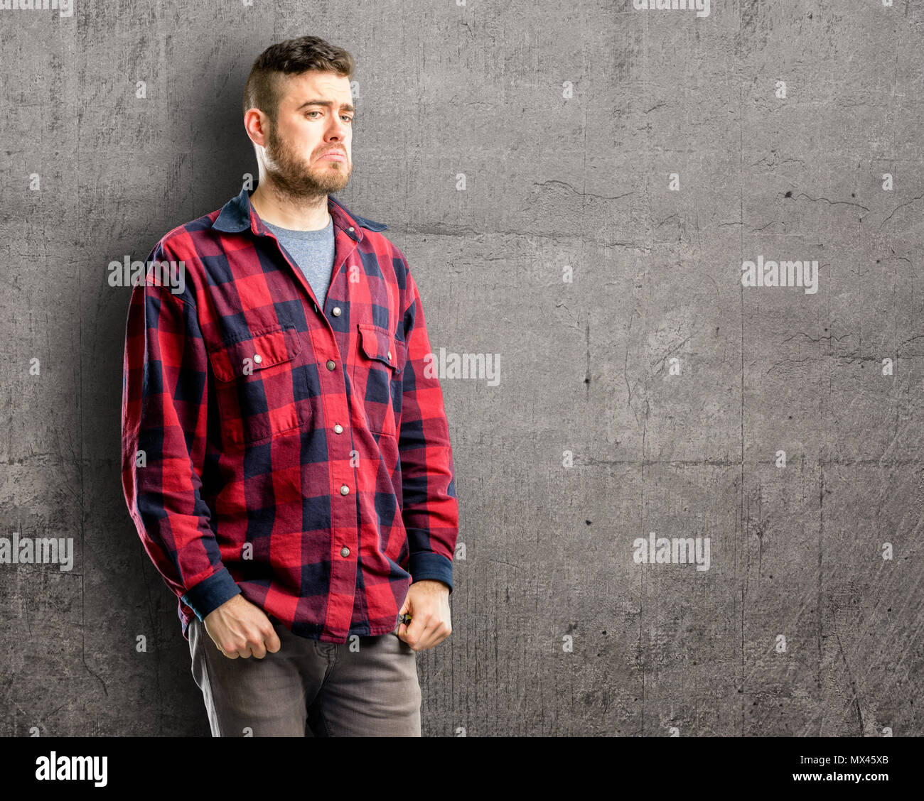 Young handsome man having skeptical and dissatisfied look expressing Distrust, skepticism and doubt - Stock Image