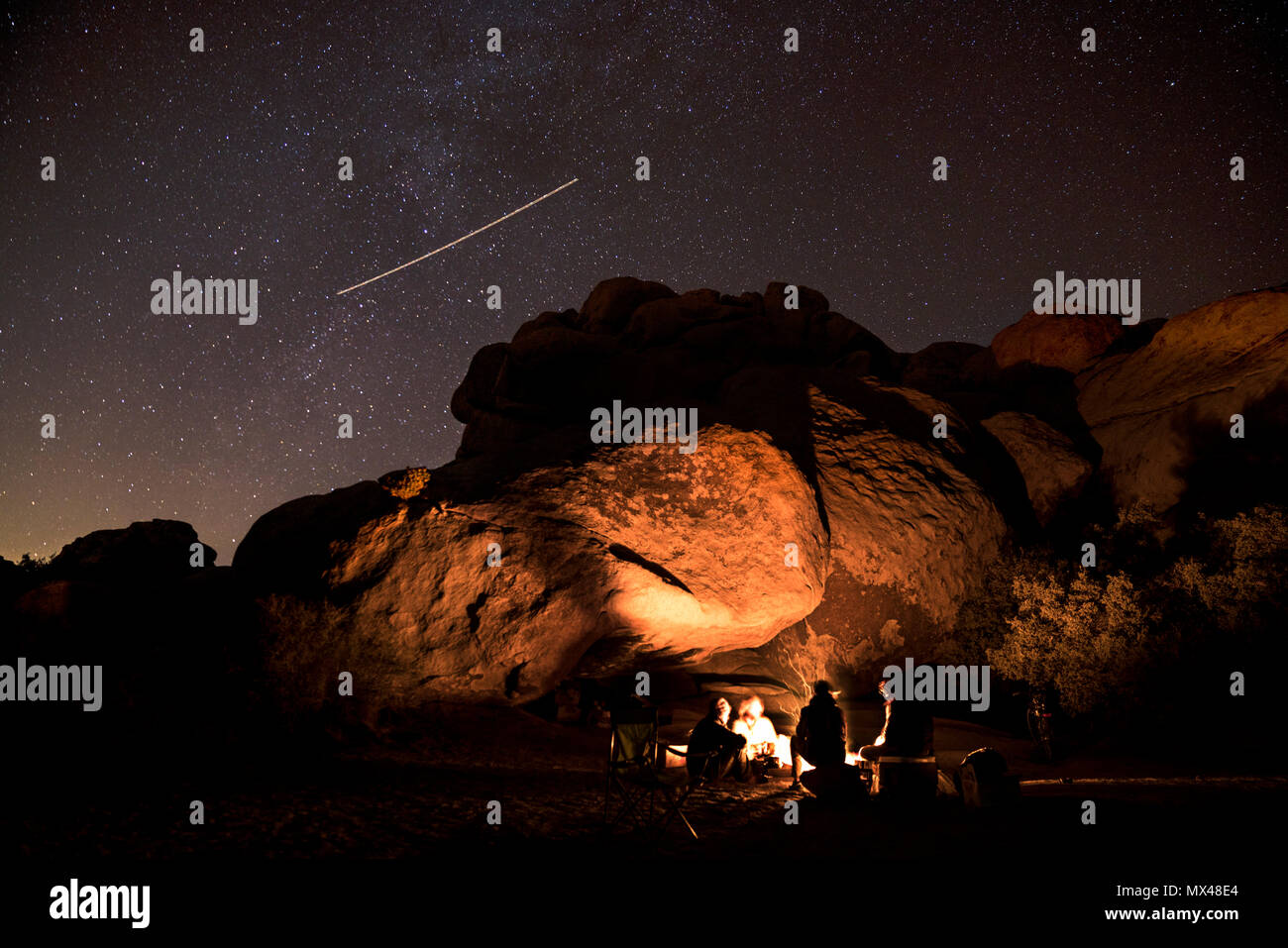 a group of climbers sit around a fire ring - Stock Image