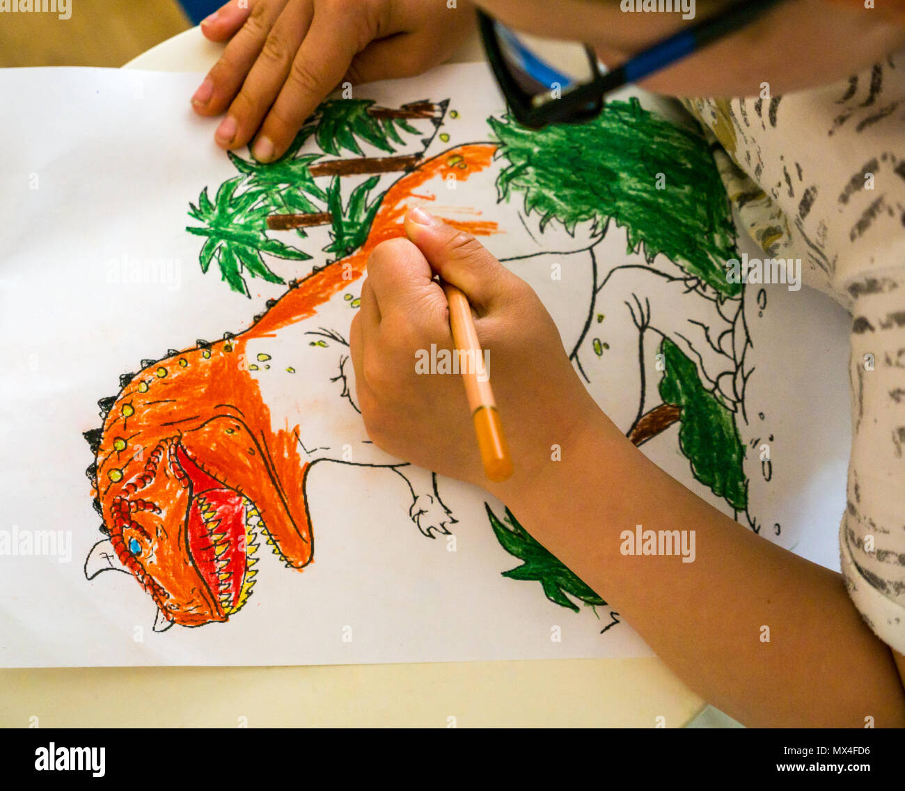 Close up of a young boy wearing glasses colouring in a picture of a ...