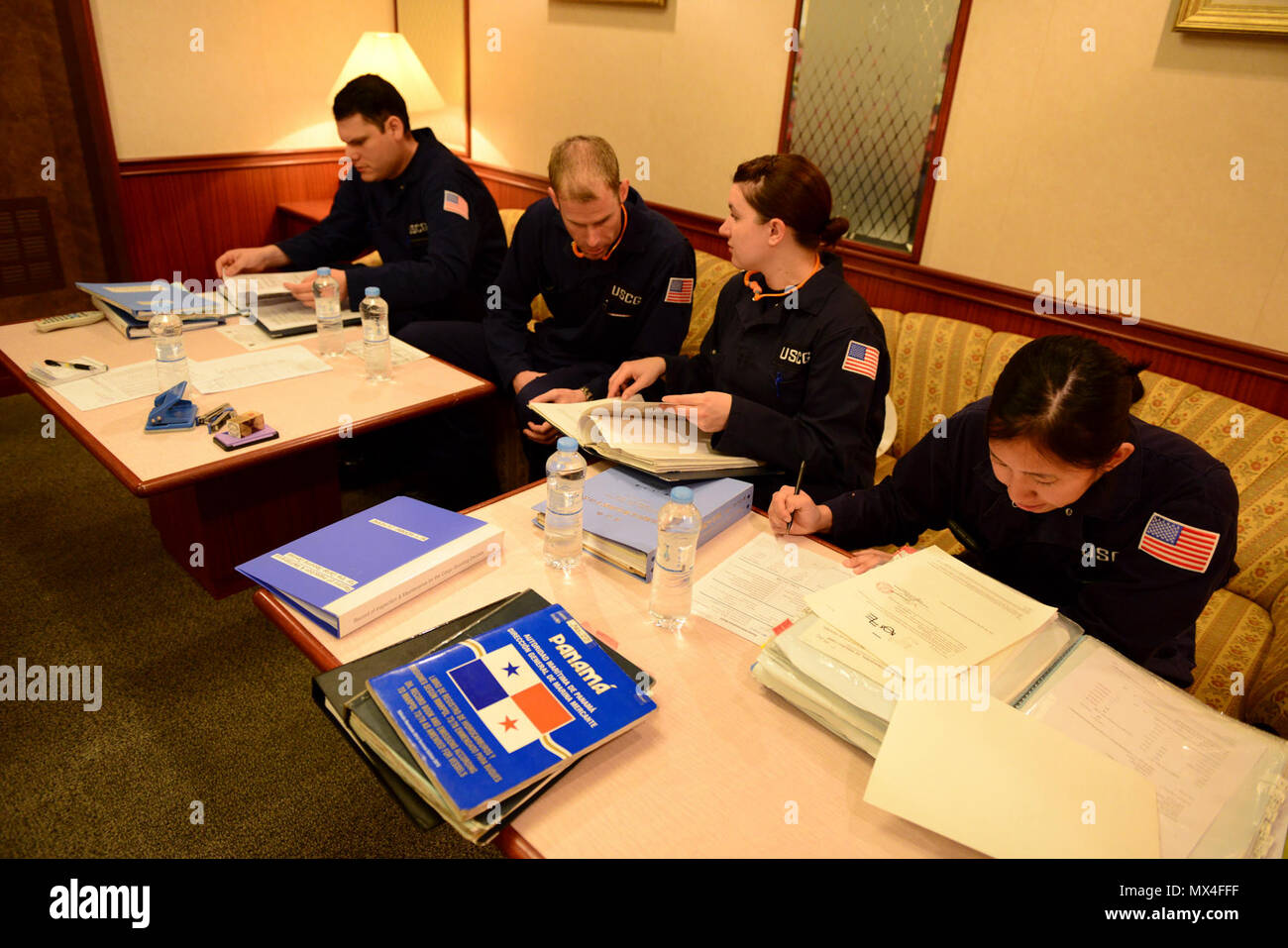Petty Officers Billy Lemos, Eric Kelley, Sarah Jacobs and Julie Imagane, marine science technicians at Coast Guard Marine Safety Unit Portland, review documents about the vessel Morning Catherine at the beginning of a Port State Control exam at the Port of Portland, Ore., May 1, 2017.    MSTs review licenses, certifications, plans and logs of a crew and their vessel prior to conducting physical inspections. - Stock Image