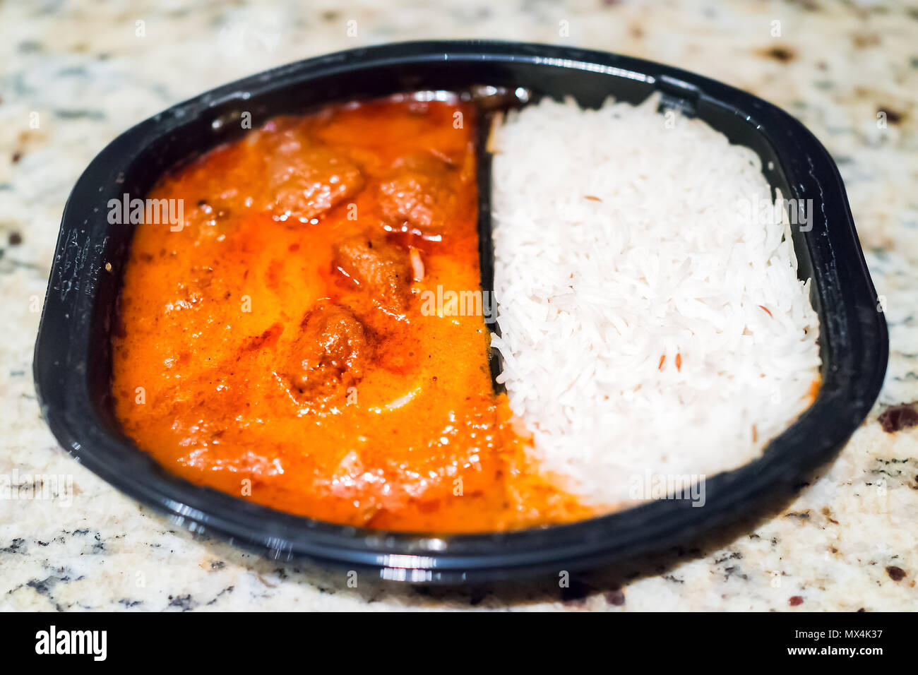 Orange red curry tikka masala sauce macro closeup, with white basmati rice in black plastic tv dinner fast food frozen meal container on table - Stock Image