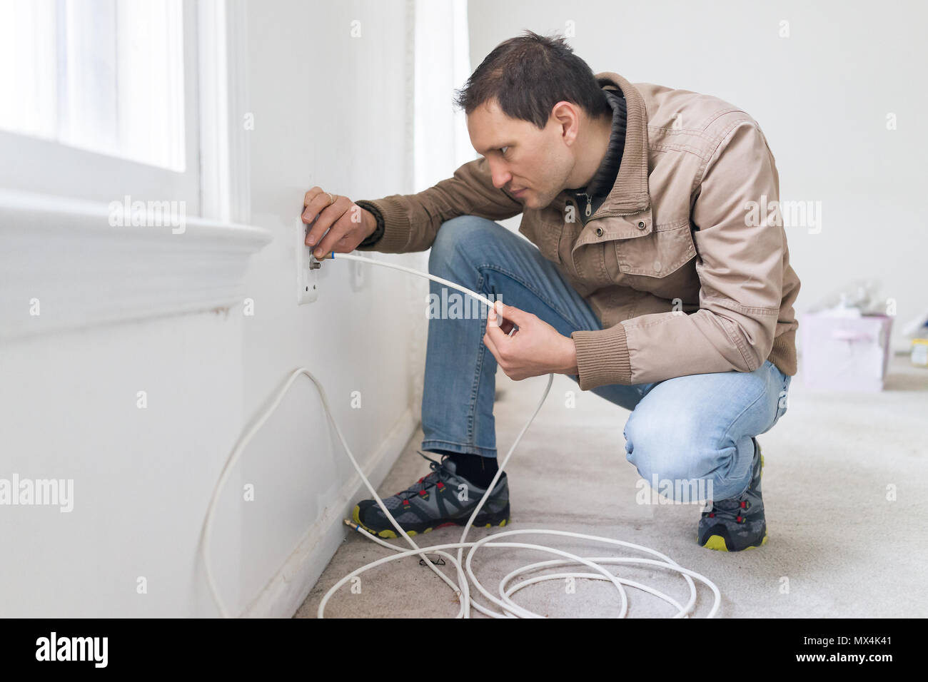 Young Man Installing Cable Television Internet Wire In Room Wall Tv Wiring Carpet Floor Flooring White Walls During Remodeling Inspection Renovation
