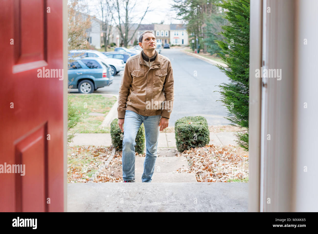 Young man standing on front porch frontyard steps in front of house home buyer looking to buy property real estate customer client in townhouse reside - Stock Image