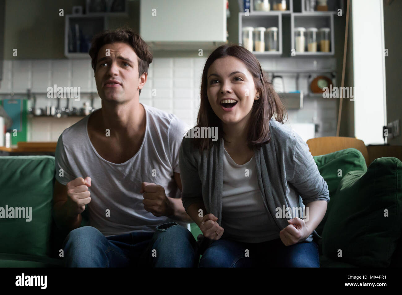 Couple cheering supporting winning team watching tv game at home - Stock Image