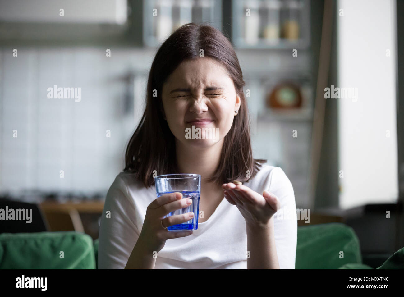 Frustrated stressed young woman grimacing afraid of taking pill  - Stock Image