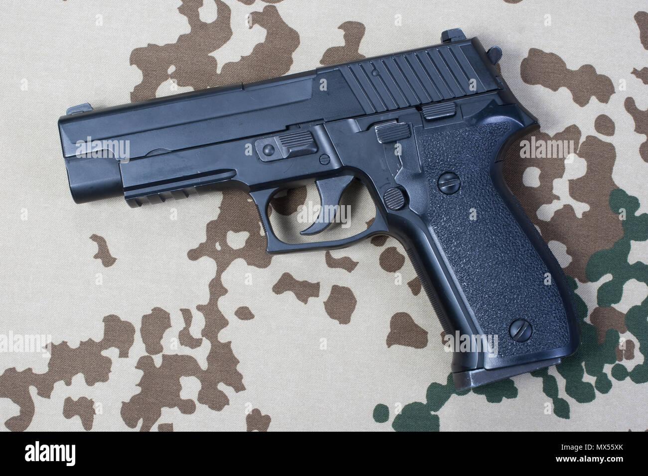 sig sauer hand gun on desert camouflaged background Stock Photo