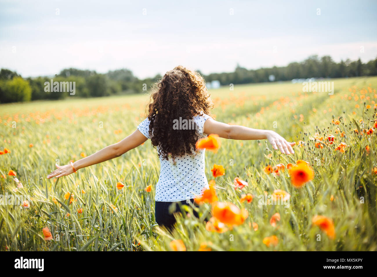 young curly carefree woman running through a field of wildflowers on a summer day - Stock Image