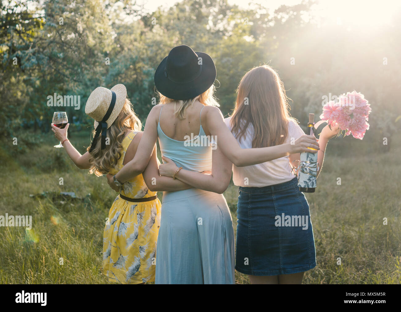 Group of girls friends making picnic outdoor. They have fun - Stock Image