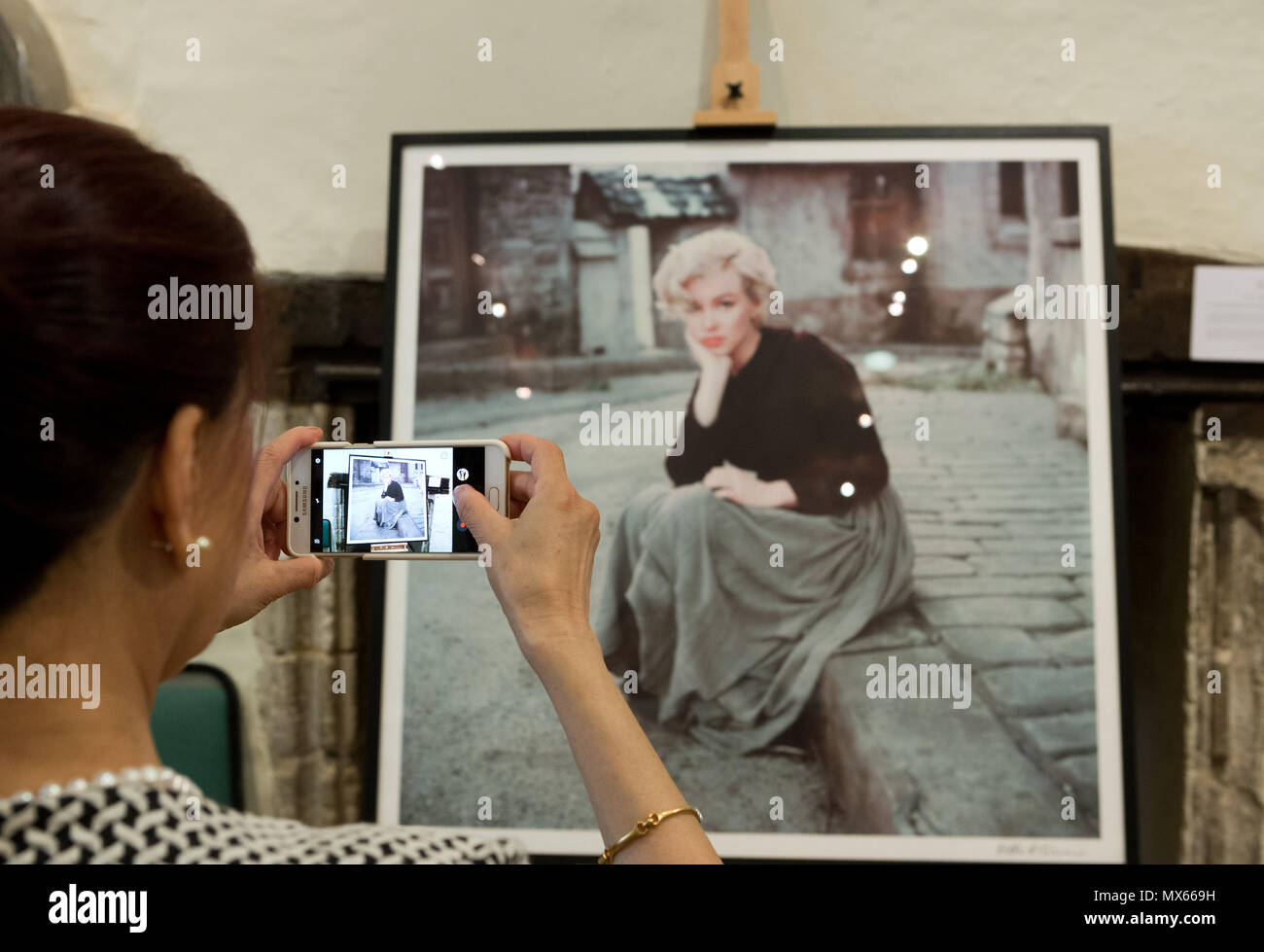 Bury St Edmunds, UK. 2nd Jun, 2018. Guest takes a photo of one of the exhibits at the 'Timeless' exhibition at Moyses Hall, Bury St Edmunds, which includes stunning images from Marilyn Monroe's very earliest days as a model, behind-the-scenes captures from her film-work, breathtaking location and studio work and emotive candid images that showcase her true personality in a unique and engaging way. Credit: Keith mindham/Alamy Live News - Stock Image