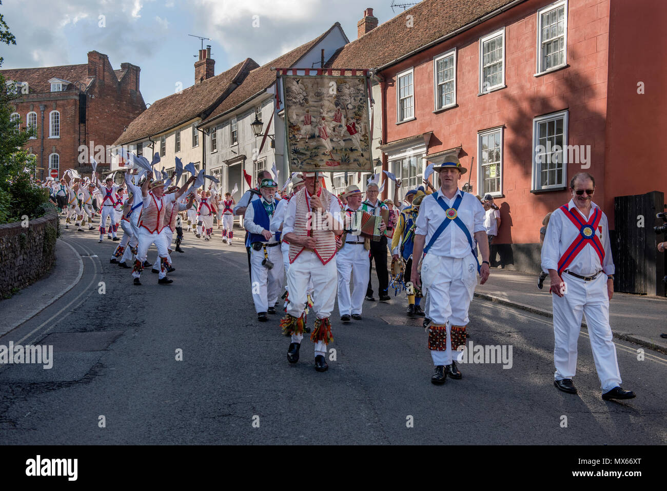 Thaxted Morris Weekend, Thaxted Essex England UK. 2-3 June 2018 The 85th Meeting of the Member Clubs of the Morris Ring hosted by Thaxted Morris Men (who wear red and white stripes) who lead the Saturday evening procession to Town Street in Thaxted after a busy day of dancing in a dozen local pubs in surrounding villages in North West Essex. Credit: BRIAN HARRIS/Alamy Live News - Stock Image