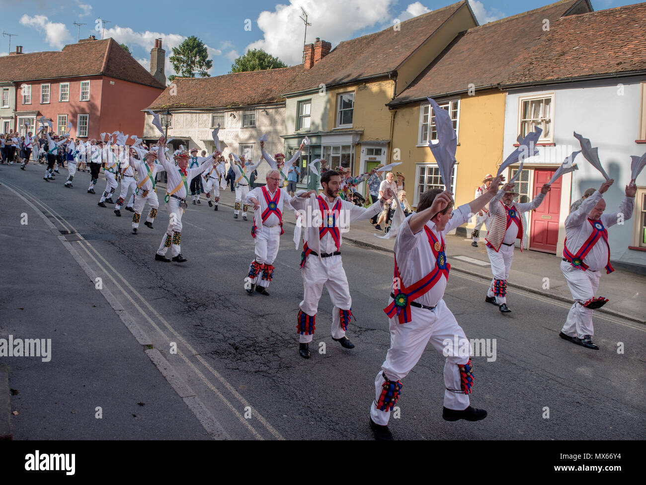 Thaxted Morris Weekend, Thaxted Essex England UK. 2-3 June 2018 The 85th Meeting of the Member Clubs of the Morris Ring hosted by Thaxted Morris Men (who wear red and white stripes) who lead the Saturday evening procession to Town Street in Thaxted after a busy day of dancing in a dozen local pubs in surrounding villages in North West Essex. The Chalice side lead Lincoln and Micklebarrow side. Credit: BRIAN HARRIS/Alamy Live News - Stock Image