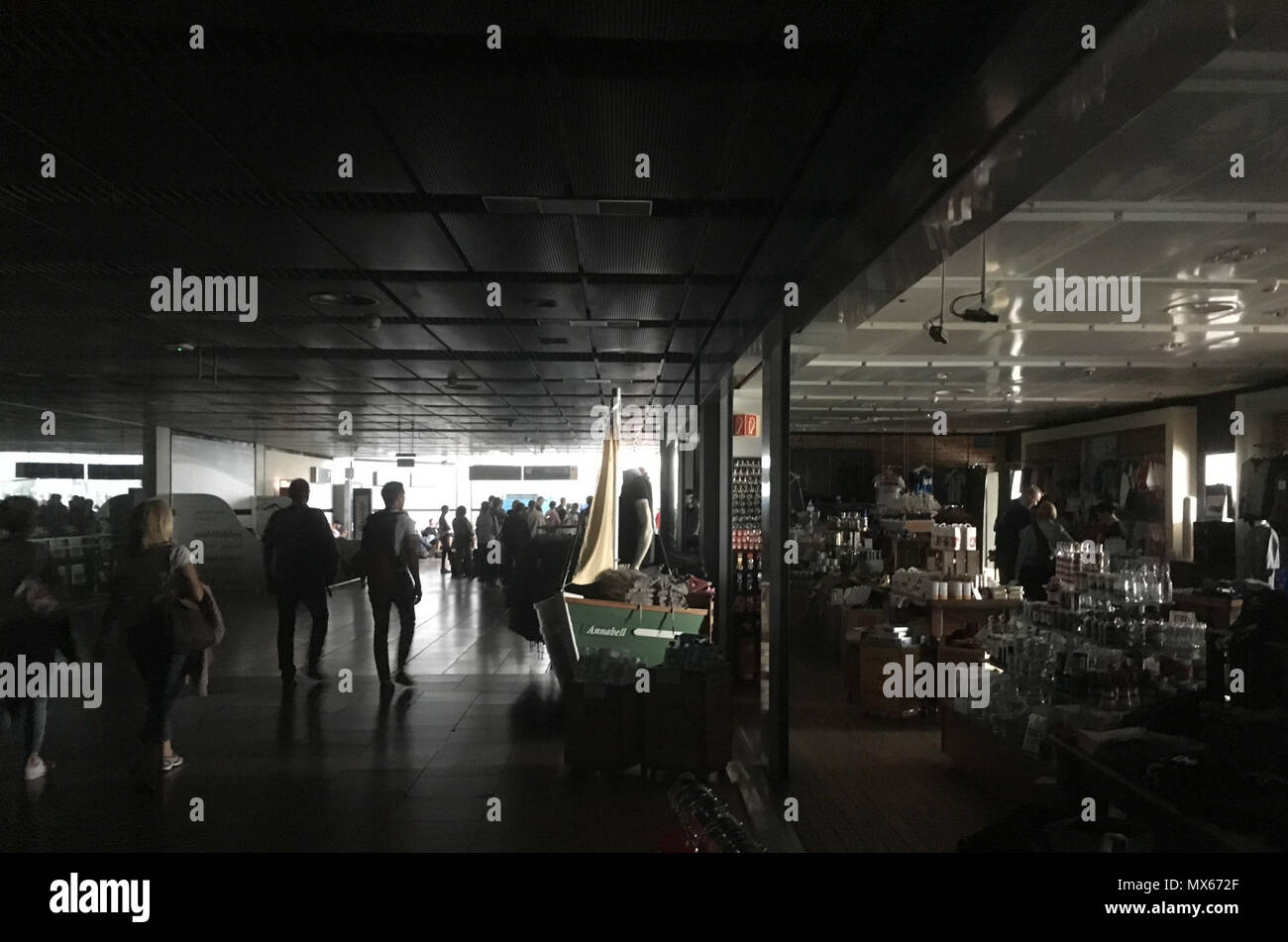 Hamburg, Germany. 03rd June, 2018. 03 June 2018, Hamburg, Germany: Travelers walk through the unlit airport during a power outage. The power outage paralyzed Hamburg Airport. Most departure switches were closed. Everywhere long lines formed. The shops were closed, the air conditioning did not work either. Credit: Thomas Müller/dpa/Alamy Live News - Stock Image
