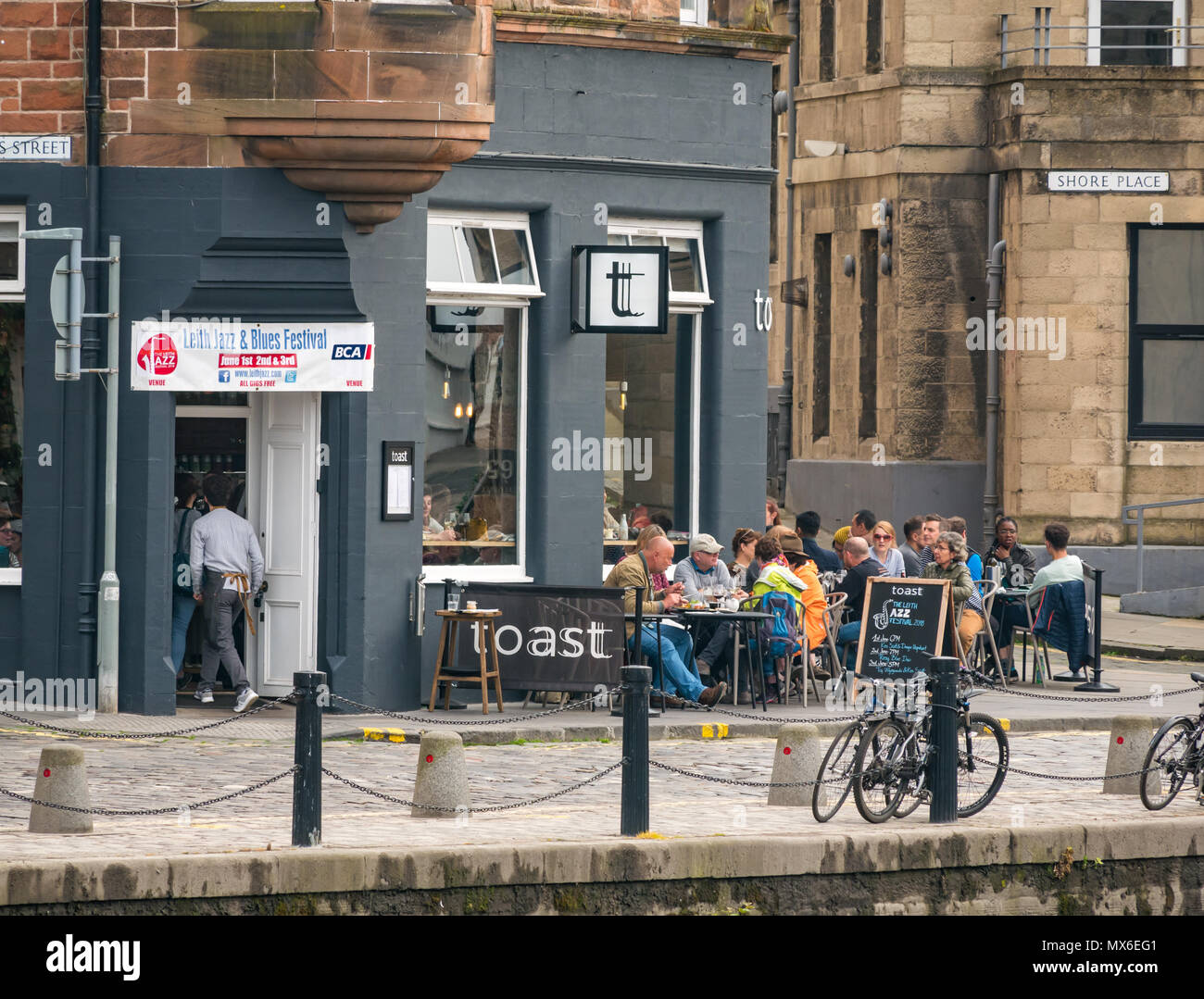 Leith Jazz & Blues Festival live music in restaurants and bars by the Water of  Leith, 3rd June 2018. The Shore, Leith, Edinburgh, Scotland, United Kingdom. The jazz and blues festival takes place over 3 weekend days. People throng the outdoor pavement tables of the restaurants and bars along the Water of Leith enjoying listening to the free live music. People at the wine bar and restaurant called Toast with the festival banner displayed - Stock Image