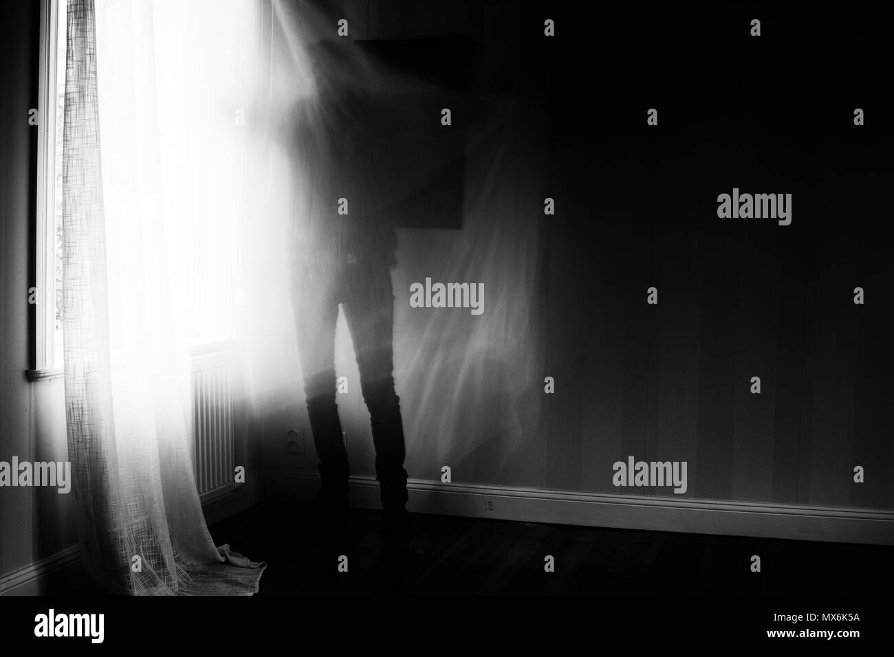 Artistic image with motion blur and grain of person standing in front of window, spooky feeling. - Stock Image