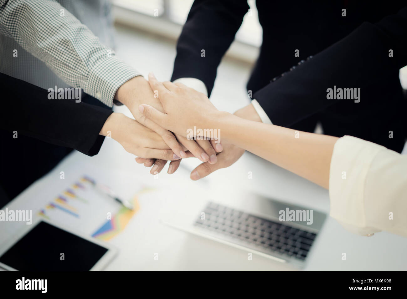 Close up top view of young business people putting their hands together. Stack of hands. Unity and teamwork concept. - Stock Image