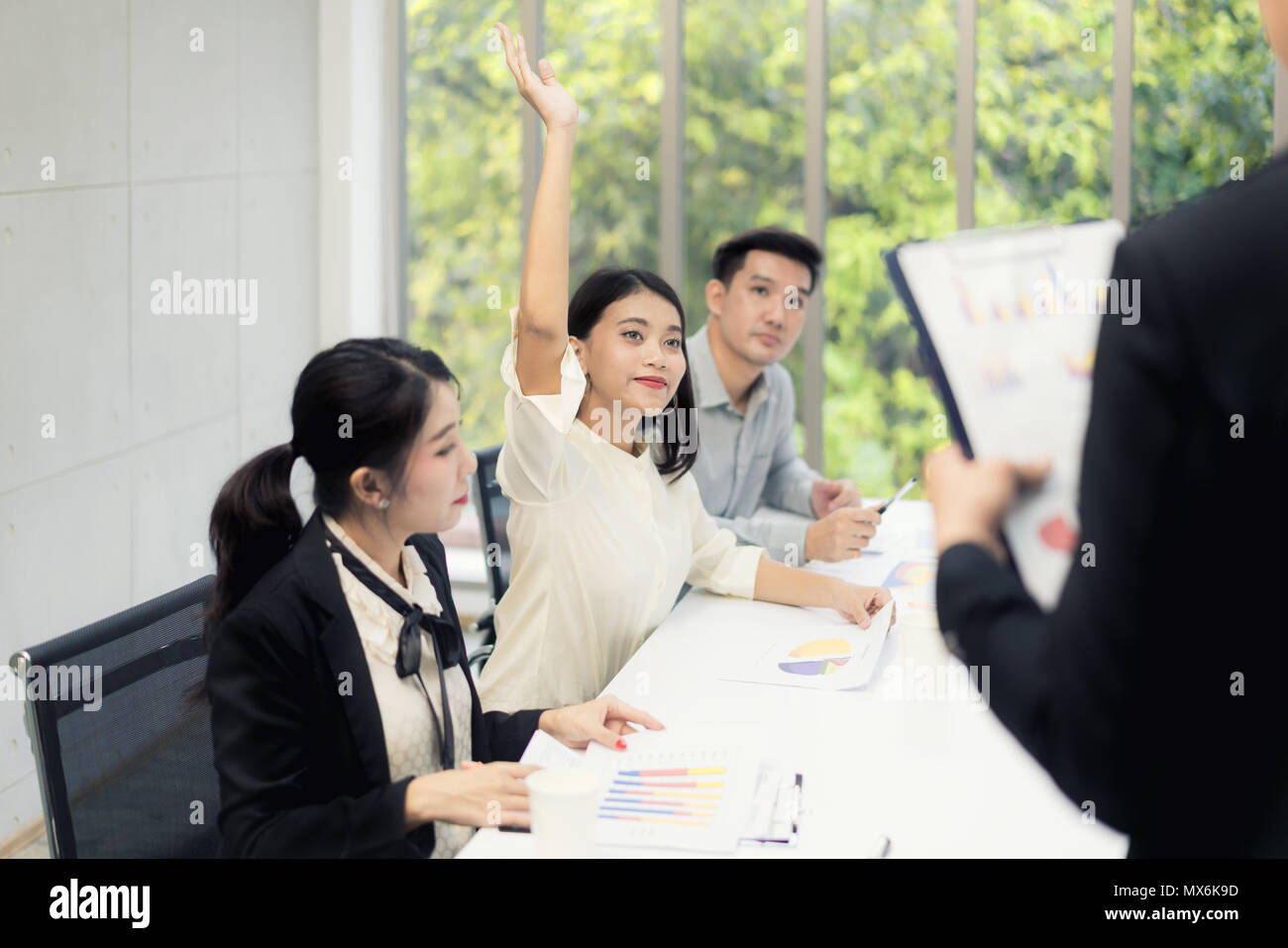 Asian woman is raising her hands has question while businessman presentation about business sale report at the meeting room - Stock Image