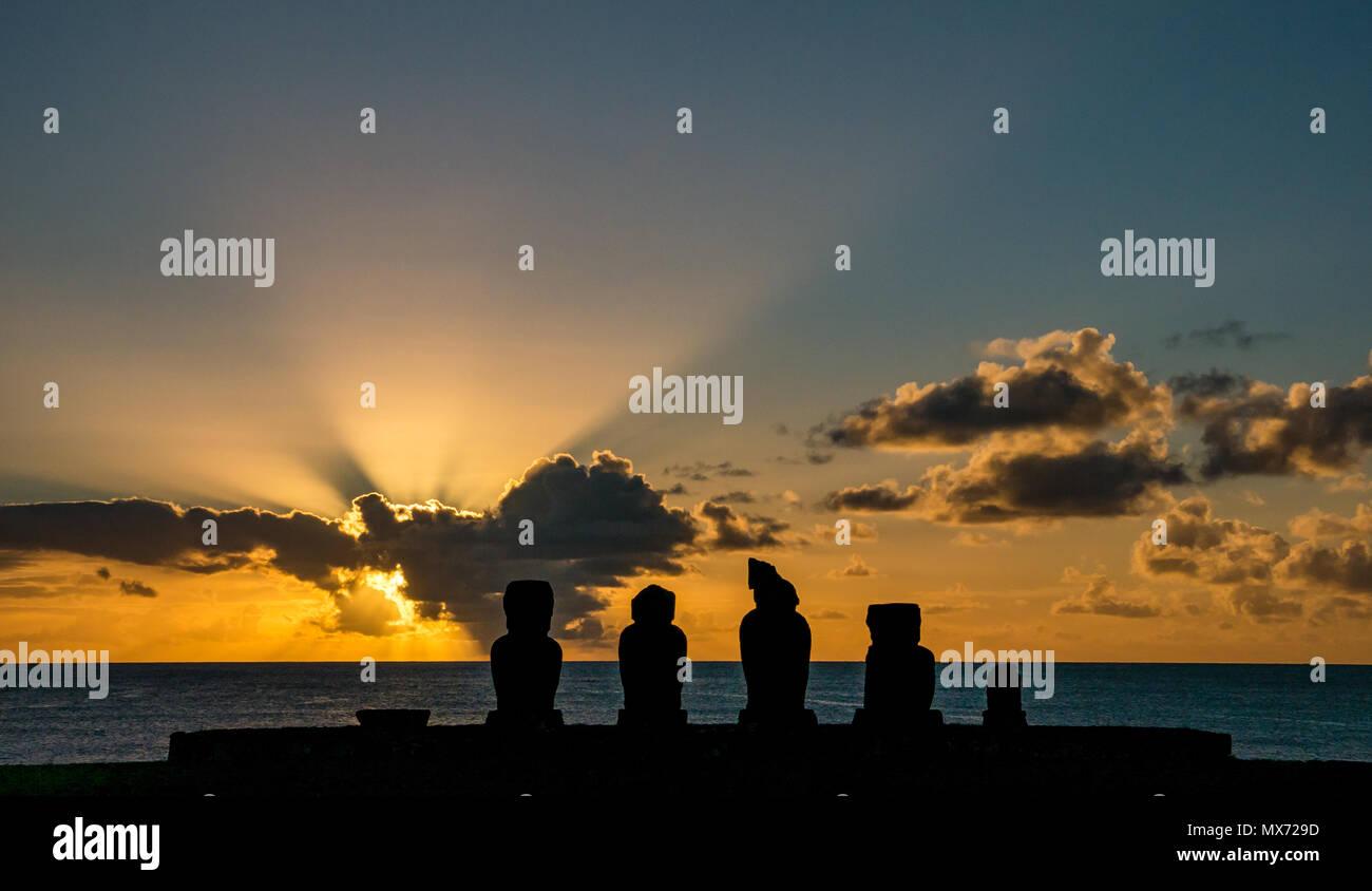 Dramatic colourful orange sunset and sunburst light with Ahu Moai silhouettes, Tahai, Hanga Roa, Easter Island, Rapa Nui, Chile - Stock Image