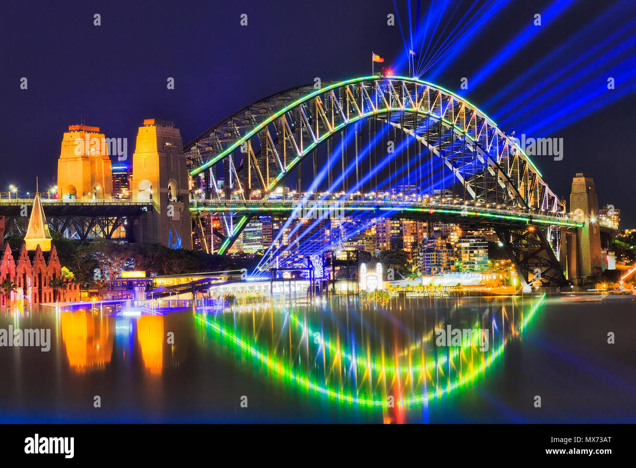 Blue bright beams of laser under arch of the Sydney harbour bridge during Vivid Sydney light show festival with reflection of lights. Stock Photo