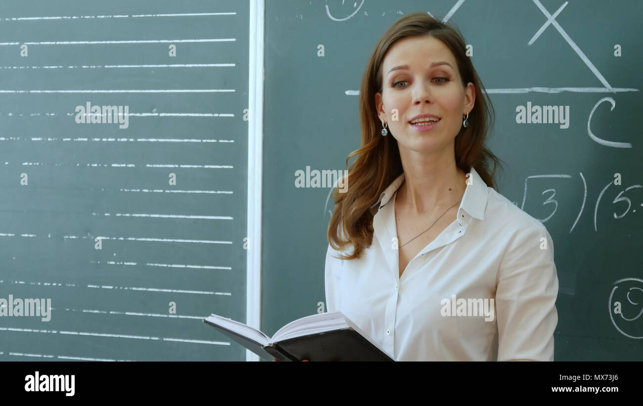 Teacher with book dictates in classroom at school. Professional shot on Lumix GH4 in with high 4K resolution. You can use it e.g in your school, educa - Stock Image